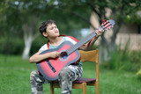 boy playing the guitar very passionary outdoors