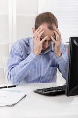 Mann mit Kopfschmerzen und Migräne im Büro