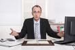 Gestresster Geschäftsmann überarbeitet am Schreibtisch