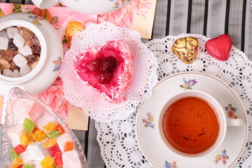 Warm cup of tea and sweets, top view