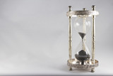 Hourglass – old fashioned hourglass, black sand, almost empty,