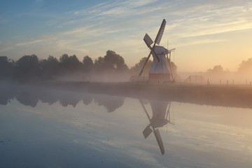 windmill in morning sunshine reflected in river
