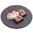 Brownies ice-cream and raspberries on slate plate isolated