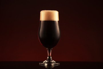 Glass of dark beer on brown background