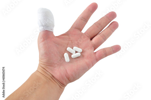 Medicines pill in hand with thumb bandage