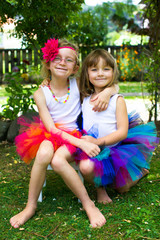 Little girls all dressed up in a colourful tutu.