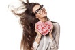 young woman with windy hair posing with a heart shape gift