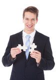 Young Businessman Holding Jigsaw Puzzle
