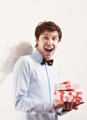 Handsome young man as cupid angel with presents
