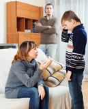 Mother and father scolding  son at living room