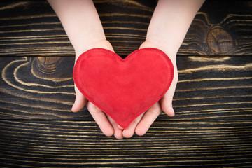 Red  heart in children's hands