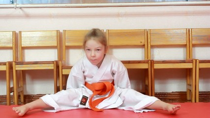 Sitting on tatami athlete doing exercises karate
