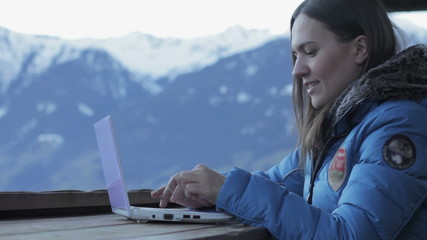 Smiling woman with laptop in the mountains