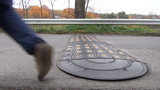 Speed bump on road cars and man pass in autumn