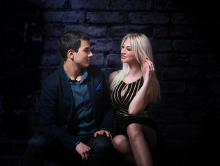 Young flirting couple, dark background