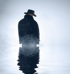person wearing trench coat and standing in water