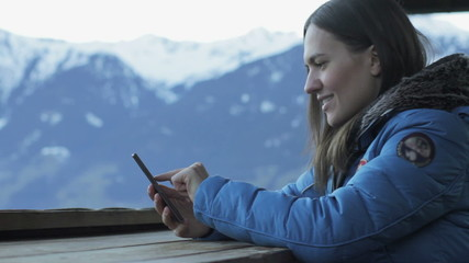 Attractive woman texting with her phone in the mountains