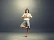 businesswoman practicing yoga over dark