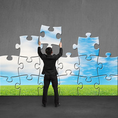 Businessman holding puzzles to assembly on concrete wall
