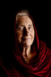 Dramatic portrait of a senior woman wearing a red shawl