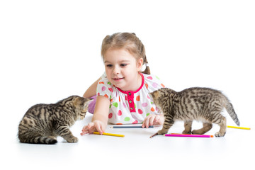 kid drawing with pencils and playing with kittens