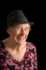Senior lady wearing a fedora laughing