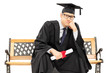 Worried college graduate sitting on bench and holding a diploma