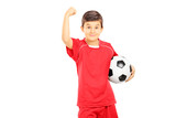 Young boy in sportswear holding soccer ball and gesturing with h