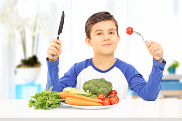 Young boy eating healthy meal seated at table