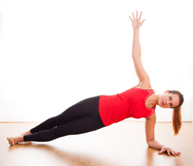 Young woman exercising - doing a side plank in a studio