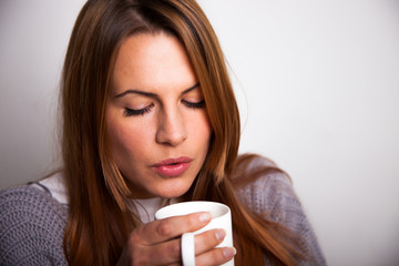 Young woman blowing on a hot mug of tea