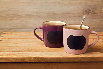 Cup of tea with chalkboard stickers on wooden table