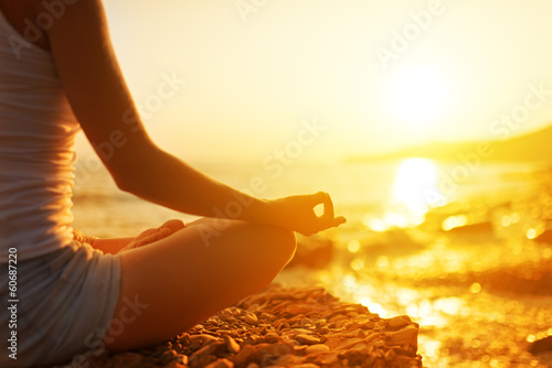 canvas print picture hand of  woman meditating in a yoga pose on beach