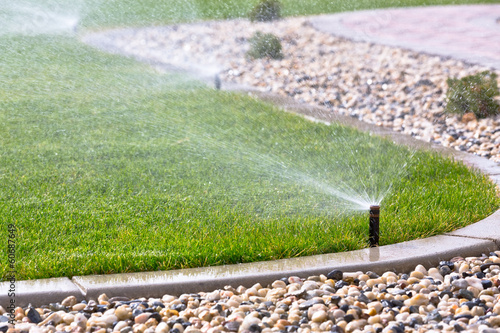 Sprinklers watering grass - 60687649