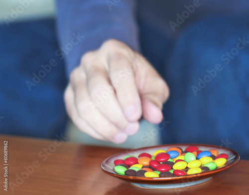 A Man Reaches for Colored Candies in a Dish