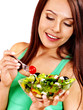 Woman eating salad at kitchen.