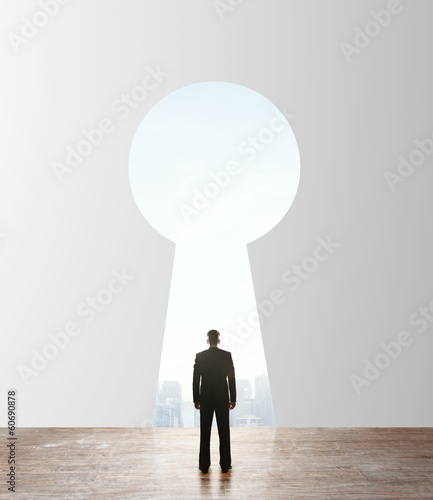 businessman looking to keyhole