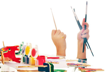 Paints and brushes in child's hands