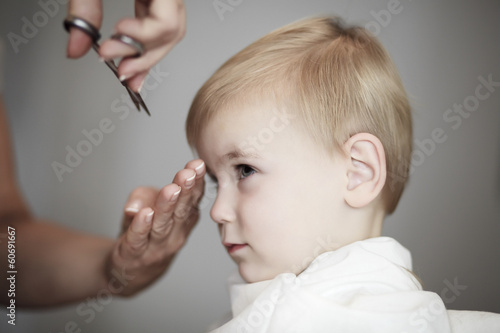 Little girl having her fist time at hairdresser