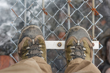 detail of walking boots on suspension bridge