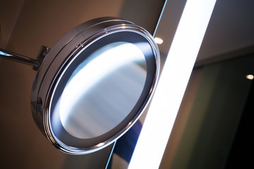 Round mirror with bright illumination in the bathroom