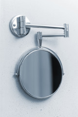 Round mirror mounted on the wall in the bathroom