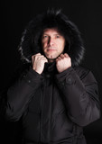 Mans portrait in winter jacket on a black background