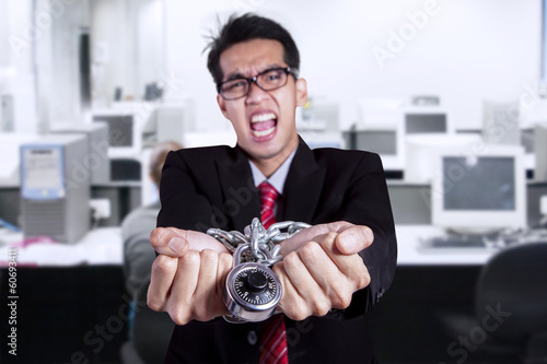 Angry businessman with hands chained at office