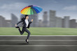 Businesswoman running with colorful umbrella