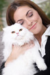 young girl hugging a white Persian cat