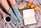 Composition with warm plaid, book, cup of hot drink and female