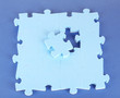 Last piece of jigsaw puzzle, close-up, on blue background