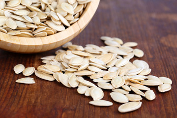 Pumpkin seeds in bowl on wooden background
