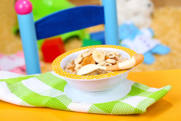 Bowl of porridge for baby and toys  on table, on toys